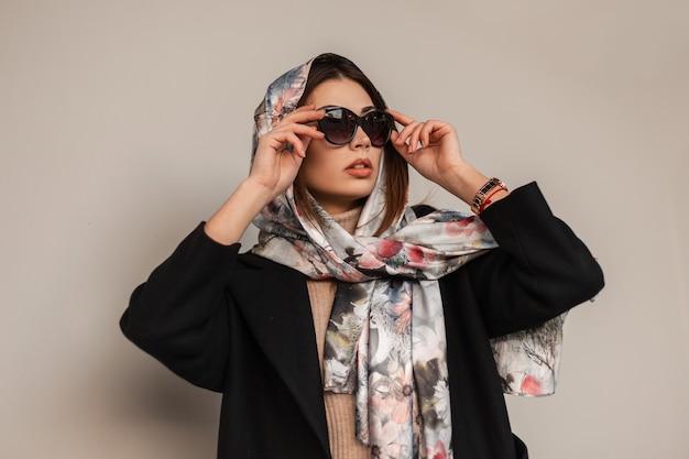 Elegante bella giovane donna in abiti alla moda in posa all'aperto. ritratto bella ragazza in occhiali da sole scuri alla moda in un cappotto con una lussuosa sciarpa di seta sulla testa vicino al muro. signora degli affari urbani.