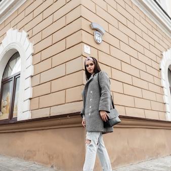 Elegante modello piuttosto giovane donna in bandana alla moda in cappotto elegante grigio con borsa nera in posa vicino all'edificio d'epoca all'aperto. la bella ragazza in vestiti primaverili casuali alla moda della gioventù gode della passeggiata.