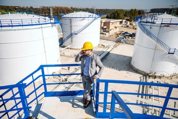 Uomo d'affari ricco elegante che ha chiamata importante circa la vendita di petrolio. esterno della raffineria.