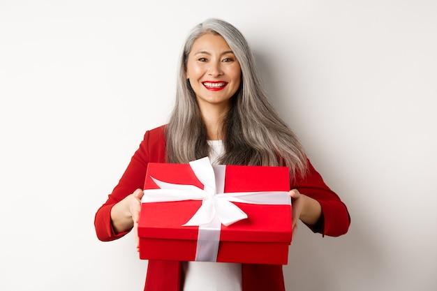 Elegante donna senior che ti dà presente. signora asiatica che tiene in mano una scatola regalo rossa e sorride, in piedi su sfondo bianco