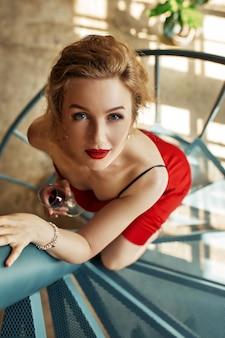 Elegante donna sexy in abito rosso e tacchi alti, rimanendo sulle scale
