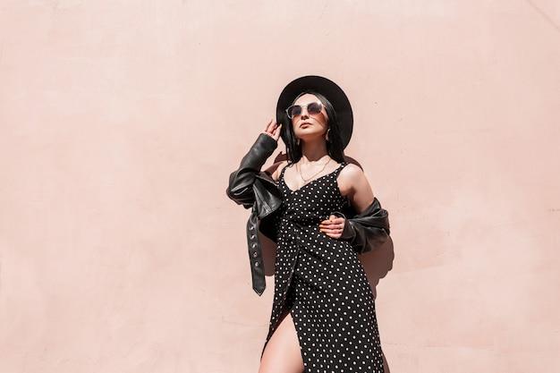Elegante giovane donna sexy in cappello elegante in bel vestito in occhiali da sole alla moda in giacca di pelle nera posa vicino alla parete vintage rosa in giornata di sole. bella ragazza in abito alla moda gode di raggi di sole.