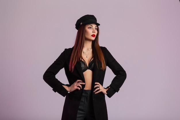 Elegante giovane donna sexy in un lungo cappotto alla moda in elegante berretto nero in pantaloni alla moda con capelli castani chic con labbra rosse gonfie in posa in studio vicino al muro. modello di moda ragazza sensuale.