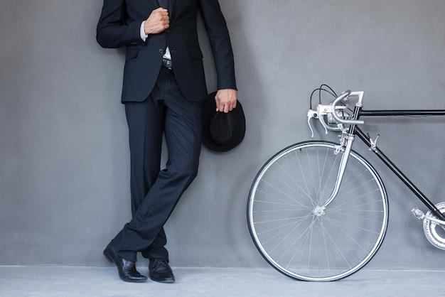 Stile elegante. primo piano di un giovane uomo d'affari che tiene in mano un cappello e si aggiusta la giacca mentre si trova vicino alla sua bicicletta su sfondo grigio