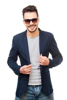 Elegante e alla moda. bel giovane che indossa occhiali da sole che si aggiusta la giacca mentre sta in piedi su sfondo bianco white