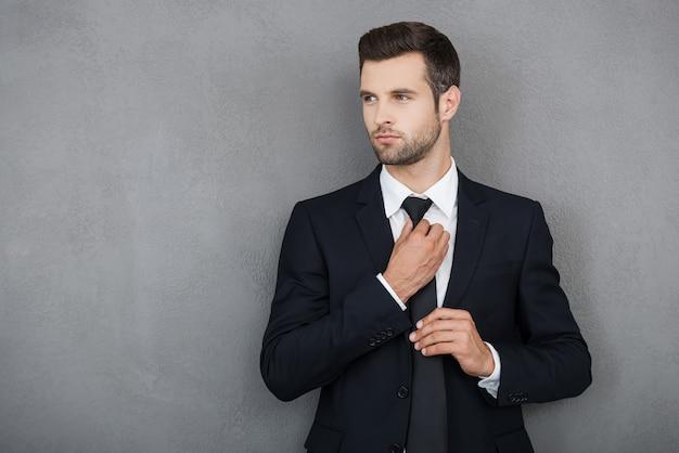 Elegante e di successo. fiducioso giovane uomo d'affari che si aggiusta la cravatta e guarda lontano mentre sta in piedi su uno sfondo grigio