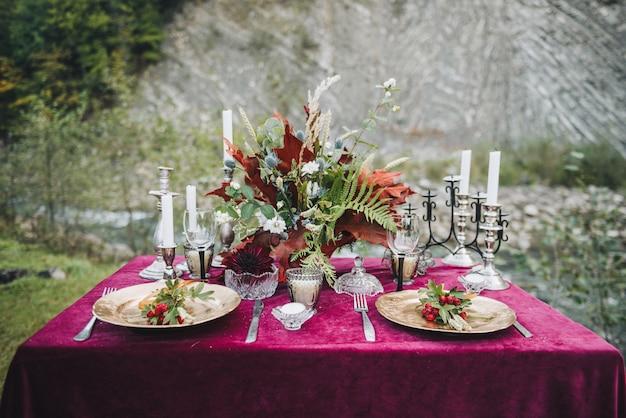 Elegante tavolo allestito per il marsala o il bordeaux per il matrimonio all'aperto