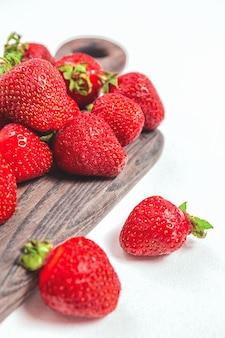 Fondo tenero elegante della fragola. bacche rosse estive mature. frutti di bosco dolci per la colazione mattutina o frutti di bosco per dessert. fragole intere su tavola di legno e sfondo bianco.