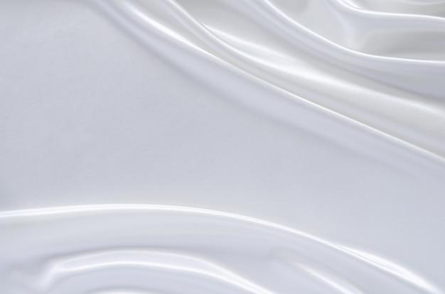 Elegante sfondo ondulato e liscio in tessuto di raso bianco