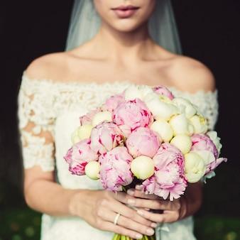 Bouquet da sposa elegante nelle mani della sposa. bouquet da sposa di peonie bianche e rosa. bouquet con nastro bianco. la mano della sposa con un anello nuziale.