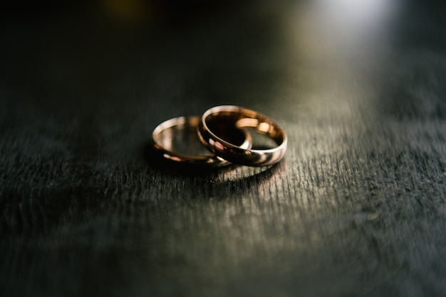 Eleganti fedi nuziali per gli sposi su uno sfondo nero con riflessi, macro, messa a fuoco selettiva