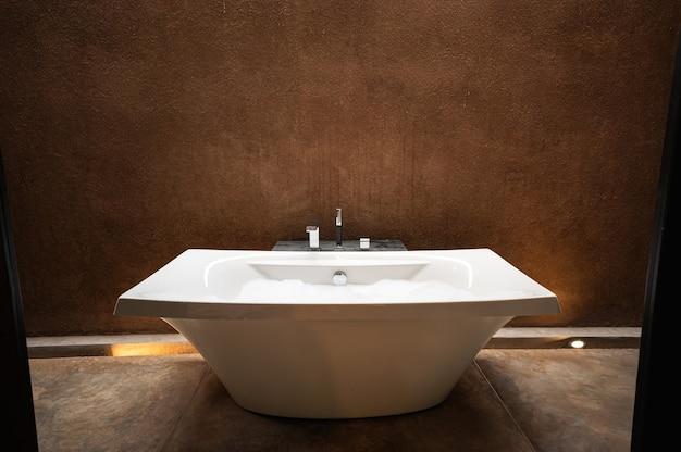 Elegante vasca da bagno in ceramica bianca con bolla in bagno dai toni naturali della terra