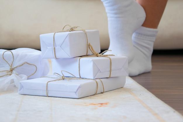 Eleganti scatole regalo bianche artigianali sul tappeto del pavimento in legno, una persona con calzini bianchi sullo sfondo