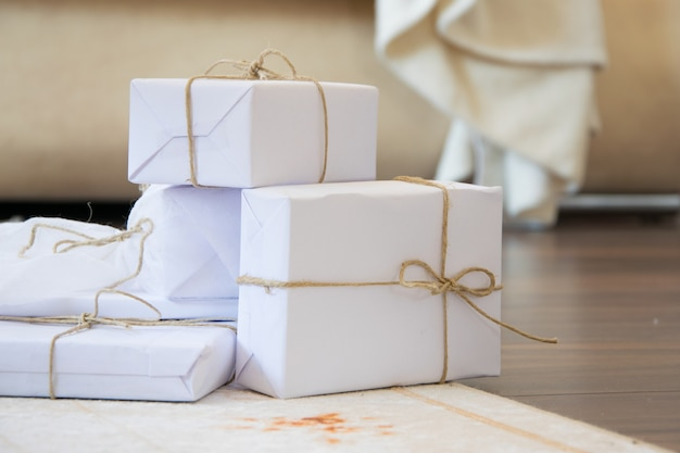 Eleganti scatole regalo artigianali bianche sul tappeto del pavimento in legno, celebrazione stagionale e concetto ecologico