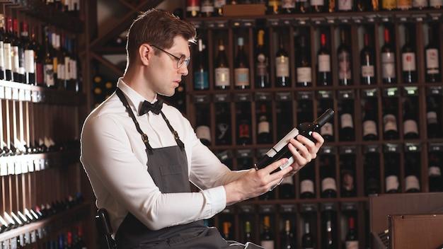Elegante venditore di vino o cavista, offre una bottiglia di vino rosso, un uomo racconta le varietà di vino, ripiani di vino in background