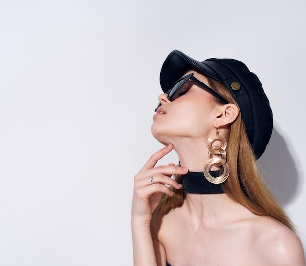Elegante donna in abito nero con occhiali scuri moda sfondo chiaro glamour.