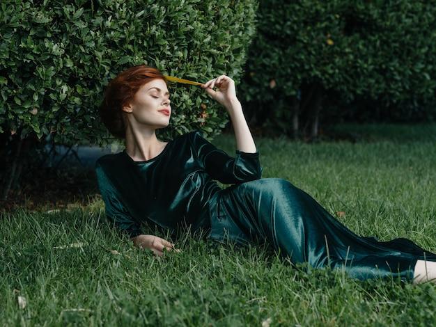 Elegante donna in abito verde si trova sul prato con fascino di viaggio d'aria fresca.