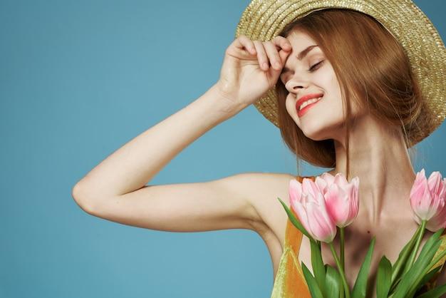 La donna elegante in un cappello con un mazzo di fiori del regalo celebra il primo piano. foto di alta qualità
