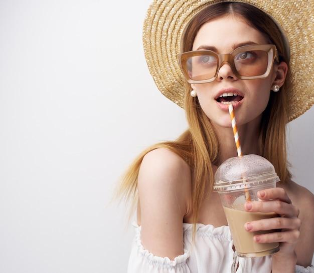 La donna elegante in un cappello con gli occhiali da sole beve il primo piano divertente