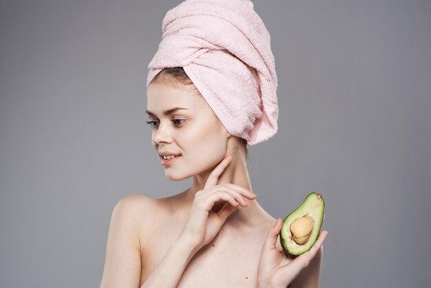 Donna elegante che tiene un tovagliolo rosa sulla sua testa nella sua mano cosmetici puliti della pelle dei frutti esotici