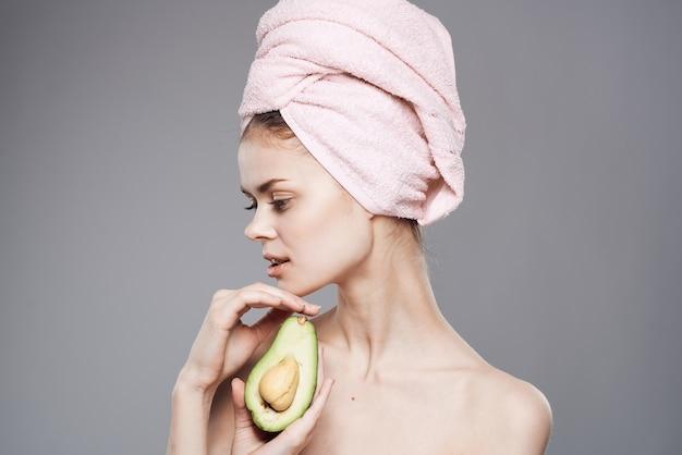 Donna elegante che tiene un tovagliolo rosa sulla sua testa nella sua mano pelle pulita dei frutti esotici