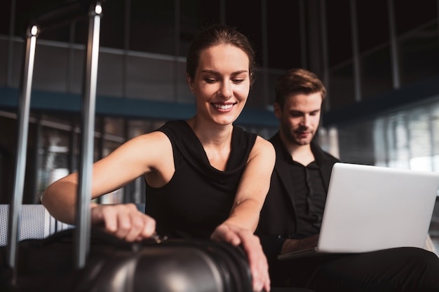 Elegante donna e uomo che lavora su un computer portatile in aeroporto