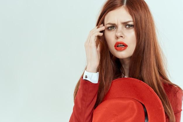 Donna elegante in cappello giacca rossa che tiene i capelli lunghi ritagliata sfondo chiaro