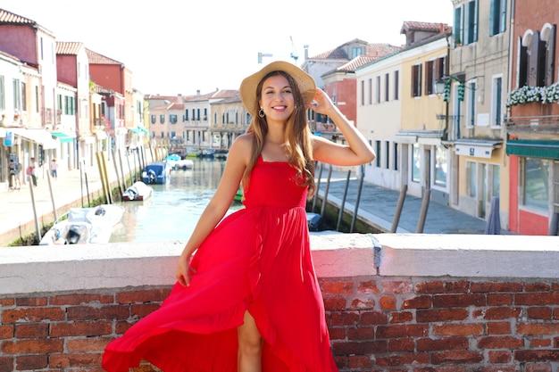 Elegante donna in abito lungo rosso camminando sul ponte nel centro storico di murano, venezia, italia