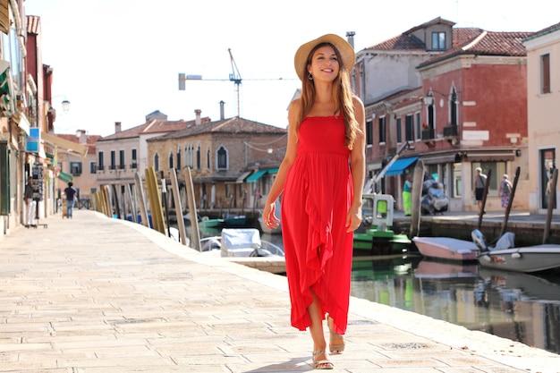 Elegante donna in abito lungo rosso a piedi nel centro storico di murano, venezia, italia