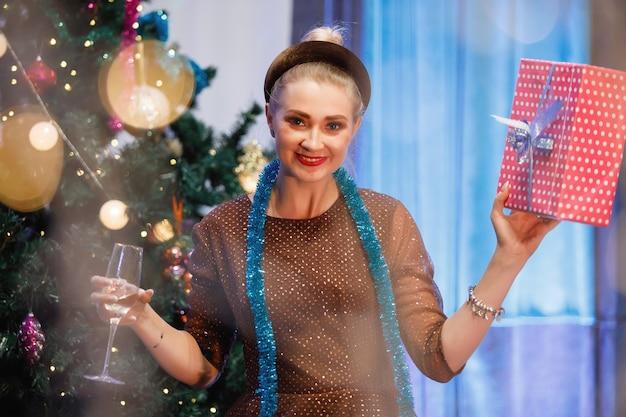 La donna elegante si rallegra con una confezione regalo vicino a un albero di natale. una donna ride, sorride, posa. filtro antirumore e grana speciale vintage, luci sfocate.