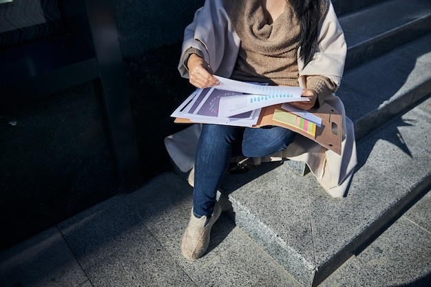 Donna elegante che studia documenti per strada
