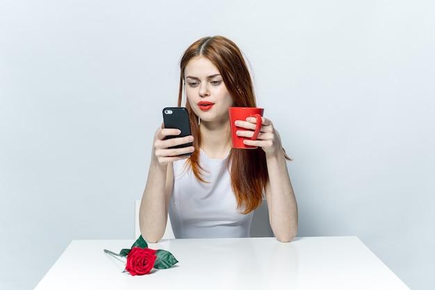 Donna elegante al tavolo con un telefono in mano a chiacchierare con una tazza di caffè