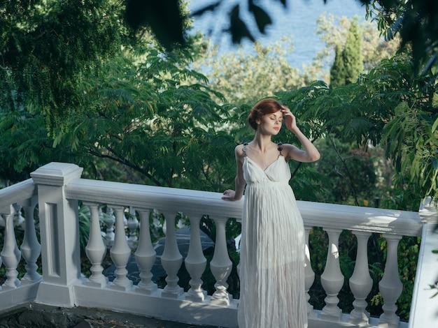 Donna elegante in abito bianco principessa greca nel parco