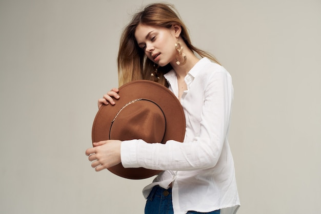 Donna elegante in camicia bianca che tiene il cappello nelle sue mani moda sfondo chiaro