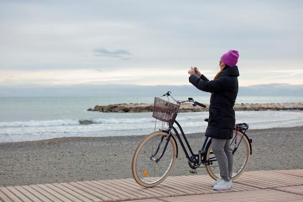 Donna elegante con la bicicletta e utilizzando un cellulare in riva al mare in una giornata invernale, spazio per il testo