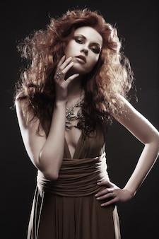Donna elegante con capelli ricci rosso vivo