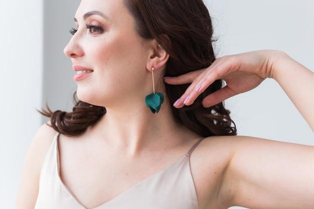 Donna elegante con orecchini, ritratto da vicino. accessori, gioielli e concetto di bigiotteria.