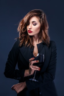 Donna elegante con bicchiere di vino rosso