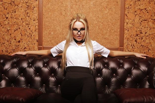 Donna elegante con gli occhiali sul divano in un interno elegante