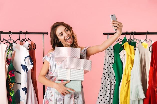 Donna elegante con acquisto in piedi in negozio vicino a stendibiancheria e prendendo selfie sul cellulare isolato in rosa
