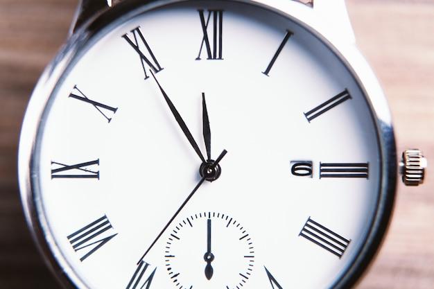 Primo piano elegante dell'orologio da polso su oscurità