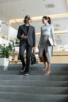 Elegante giovane donna d'affari asiatica con laptop piegato che ascolta un collega maschio maturo mentre entrambi si muovono al piano di sotto dopo il lavoro