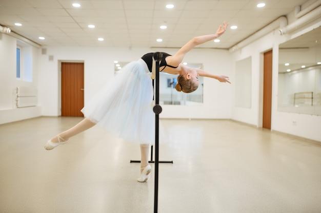 Elegante giovane ballerina che prova alla sbarra in classe