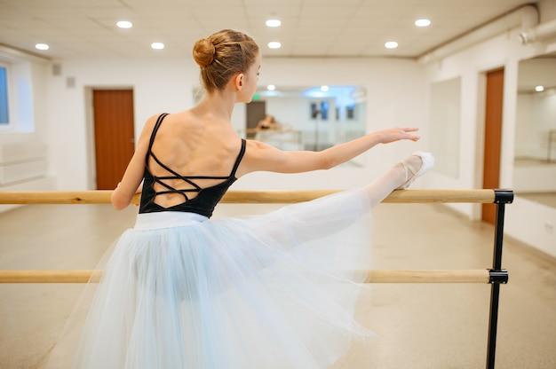 Elegante giovane ballerina lavora alla sbarra in classe