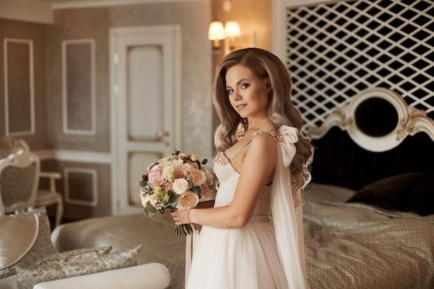 Elegante giovane sposa in abito avorio mantenendo il bellissimo bouquet
