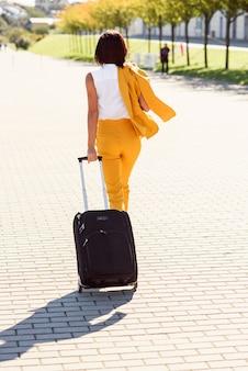 La giovane donna elegante di affari in vestito giallo alla moda si affretta ad una riunione d'affari e tira una valigia, vista dalla parte posteriore.