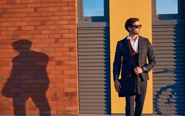 Elegante giovane uomo d'affari che cammina sulla strada della città