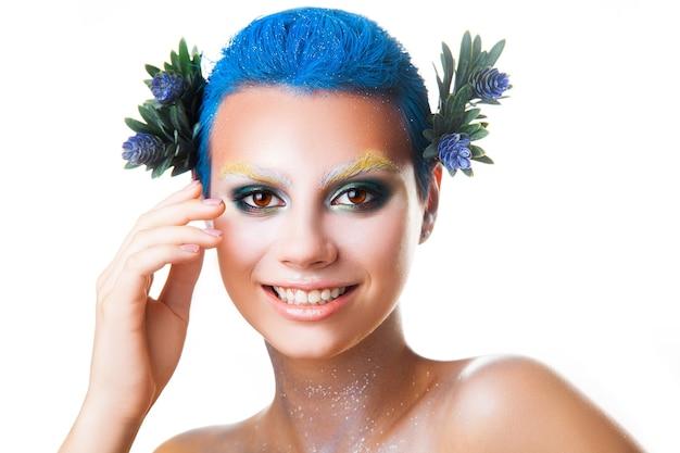 Ragazza elegante con trucco multicolore che sorride sul colpo dello studio della macchina fotografica isolato