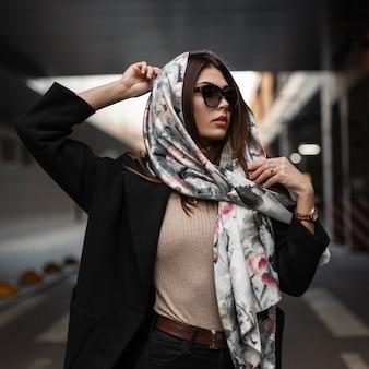 Elegante giovane donna abbastanza bella in eleganti occhiali da sole scuri in un cappotto nero mette una lussuosa sciarpa di seta sulla testa all'aperto. modello di moda bella ragazza in posa sulla strada in città. signora sexy.
