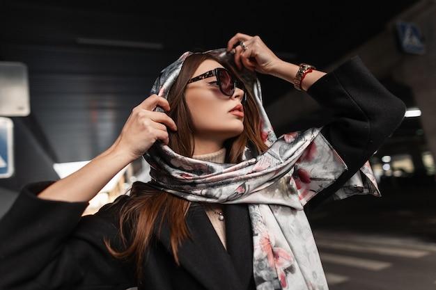 Elegante giovane donna abbastanza bella in eleganti occhiali da sole scuri in un cappotto nero mette una lussuosa sciarpa di seta sulla testa all'aperto. modello di moda bella ragazza si rilassa sulla strada in città. signora sexy.